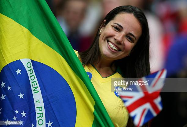 Brazil fan smiles as she poses with the country's national flag next to a Union Jack during the Women's Football first round Group E Match between...