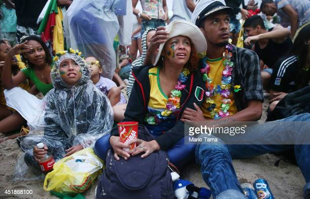 Brazil fans are devastated while watching the first half on Copacabana Beach during the 2014 FIFA World Cup semi-final match between Brazil and...