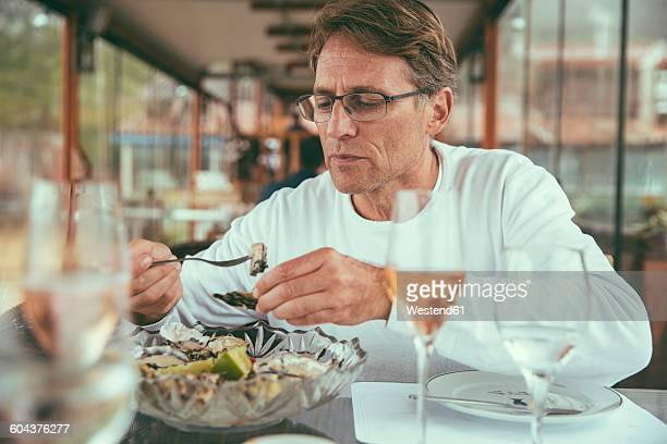 Brazil, Florianopolis, man eating fresh oysters in a restaurant