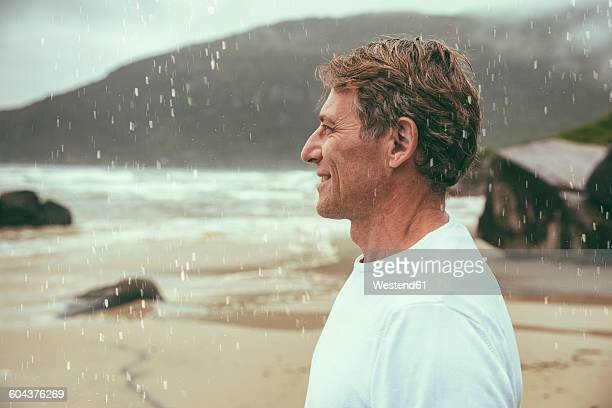 Brazil, Florianopolis, profile of happy man standing in the rain on the beach