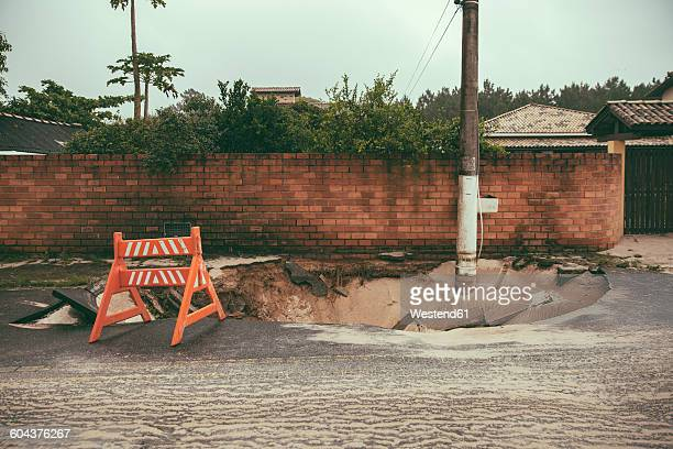Brazil, Florianopolis, traffic barrier on broken tarmac after heavy rainfalls