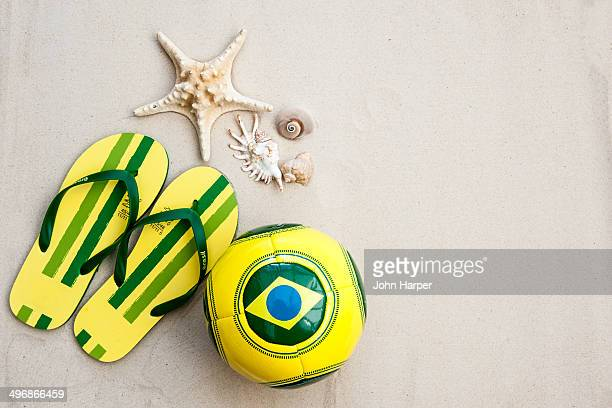 Brazil football, flip flops and shells on sand