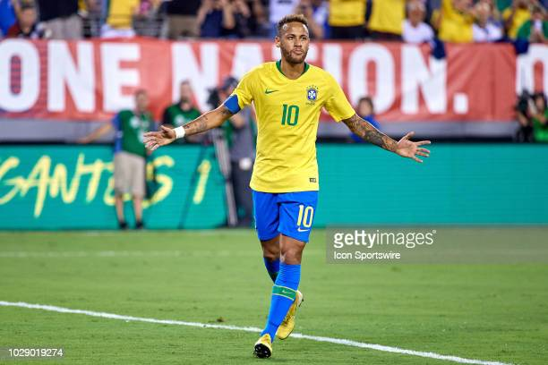 Brazil forward Neymar celebrates with fans and teammates after scoring a goal from taking a penalty kick in the first half of game action during the...