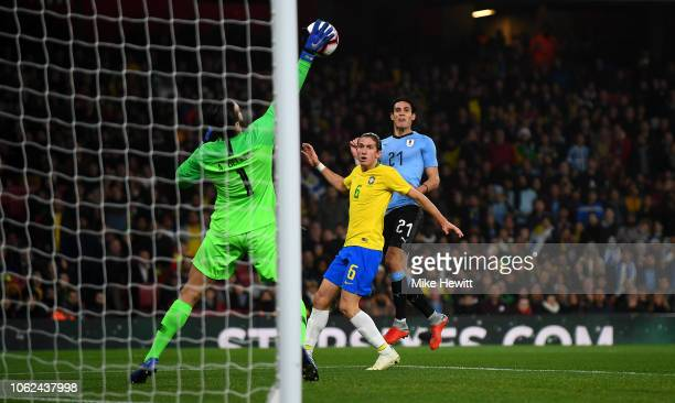 Brazil goalkeeper Alisson saves a shot from Edinson Cavani of Uruguay as Filipe Luis looks on during the International Friendly between Brazil and...