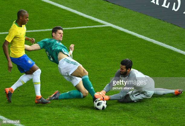 Brazil goalkeeper Alisson saves from Germany's Mario Gomez during the international friendly soccer match between Germany and Brazil at the...