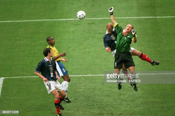 Brazil goalkeeper Taffarel punches clear from Scotland's Gordon Durie as Brazil's Cesar Sampaio and Scotland's Christian Dailly look on