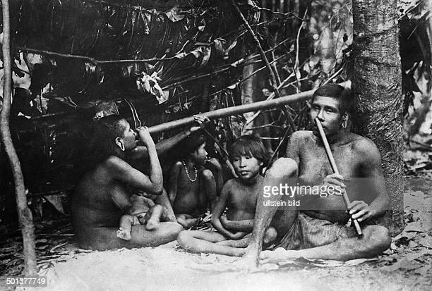 Brazil indians playing on a bamboo flute date unknown