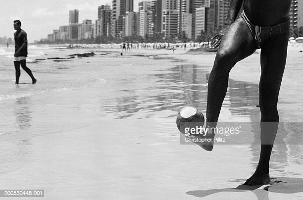 Brazil, man playing football on beach with coconut (B&W)
