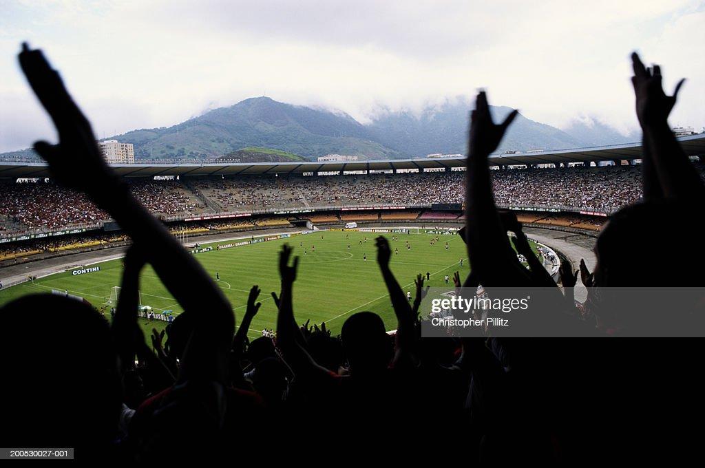 Brazil, Maracana Stadium, football fans cheering in foreground : Stock-Foto