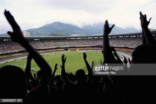 Brazil, Maracana Stadium, football fans cheering in foreground