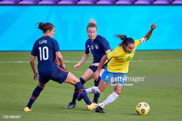 Brazil midfielder Marta battles with United States forward Carli Lloyd and United States defender Becky Sauerbrunn in action during a SheBelieves Cup...