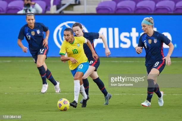 Brazil midfielder Marta dribbles the ball dribbles past United States midfielder Julie Ertz and United States midfielder Rose Lavelle in action...