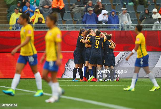 Brazil players look dejected as Kyah Simon of Australia celebrates with team mates as she scores their first goal during the FIFA Women's World Cup...