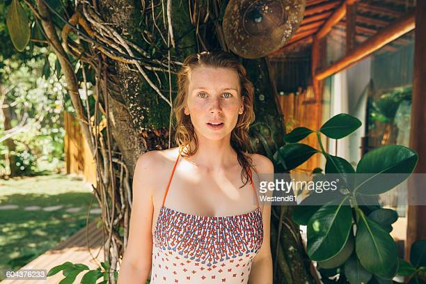 Brazil, Porto Seguro, portrait of woman wearing bathing suit standing in front of a tree