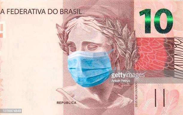 brazil quarantine, 10 reals banknote with medical mask. the concept of epidemic and protection against coronavrius. - economia - fotografias e filmes do acervo
