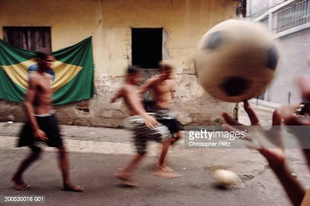 Brazil, Rio de Janeiro, boys playing football in street