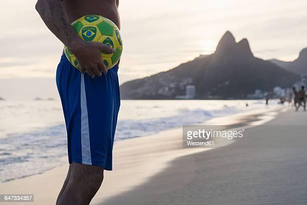 Brazil, Rio De Janeiro, man holding ball on Ipanema beach