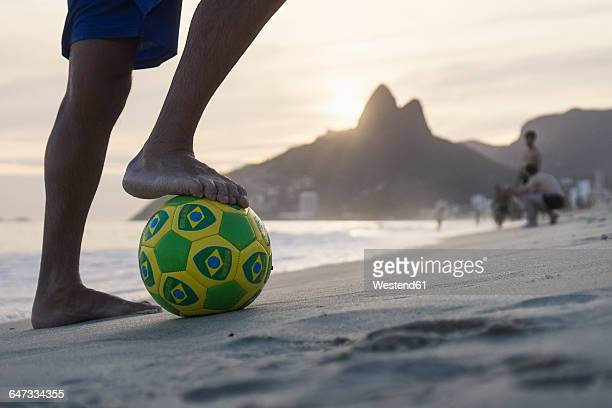 brazil, rio de janeiro, man standing with ball on ipanema beach - ビーチサッカー ストックフォトと画像