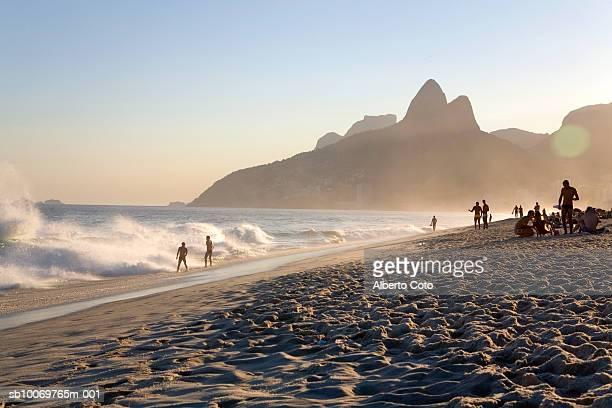 brazil, rio de janeiro, people on panema beach near dois irmaos at sunset - rio de janeiro imagens e fotografias de stock