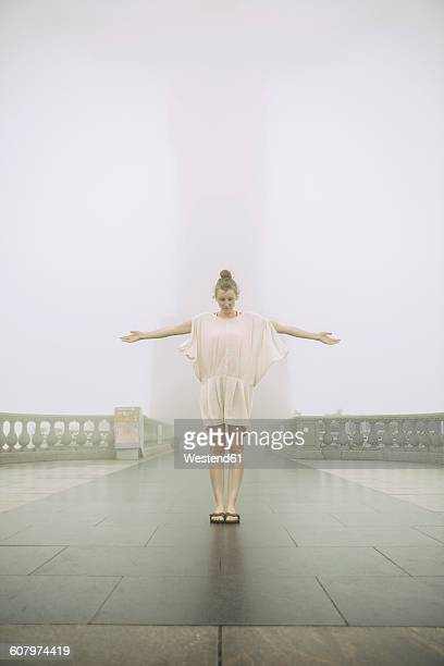Brazil, Rio de Janeiro, woman impersonating Christ the Redeemer on a hazy day