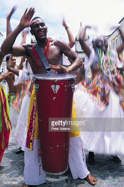 Brazil, Salvador, man beating drum surrounded by dancers (blurred moti
