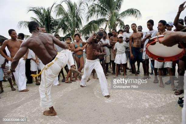 Brazil, Salvador, men performing capoeira on beach to music