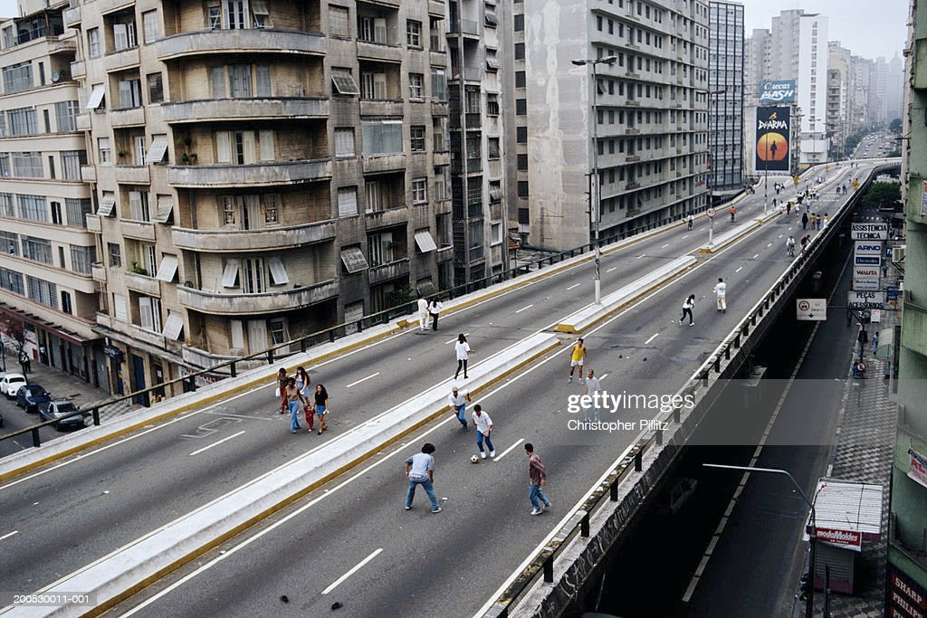 Brazil, Sao Paolo, people playing football on city highway : Stock Photo