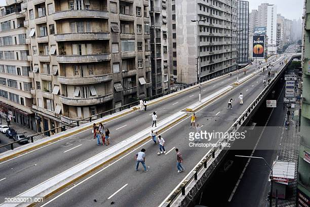 Brazil, Sao Paolo, people playing football on city highway