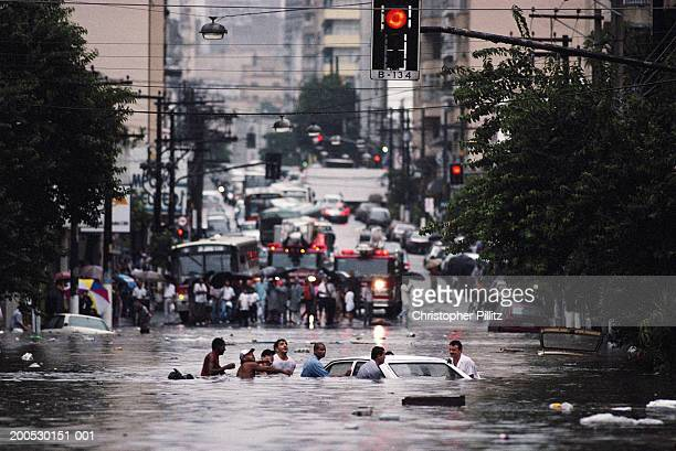 Brazil, Sao Paolo sity people surrounding car in flooded street