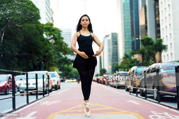 Brazil, Sao Paulo, Ballet dancer standing on tiptoes on bicycle lane