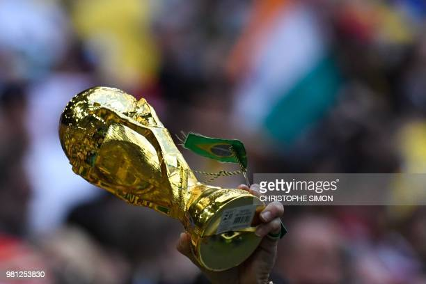 Brazil supporter carries a replica of the World Cup as he celebrates during the Russia 2018 World Cup Group E football match between Brazil and Costa...