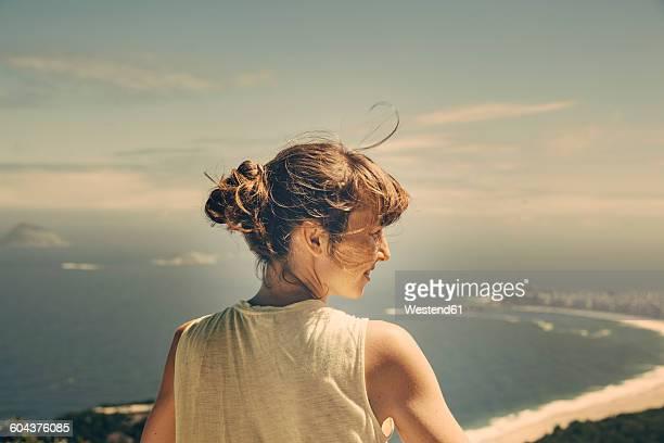 Brazil, Woman looking down onto Copacabana of Rio de Janeiro from Sugarloaf Mountain