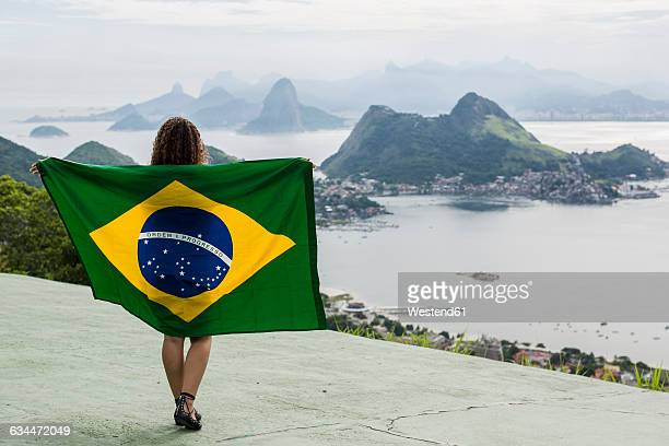 Brazil, woman with Brazilian flag on a viewpoint in Rio de Janeiro