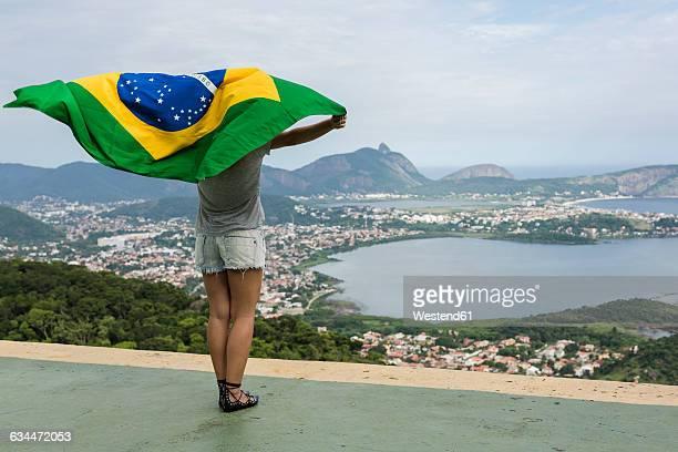 Brazil, woman with Brazilian flag on a viewpoint in Rio de Janeiro