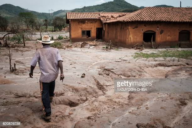 Brazilian 76yearold farmer Jose Pascual walks through a devastated area in Paracatu de Baixo village which has been ruined by the flood following the...