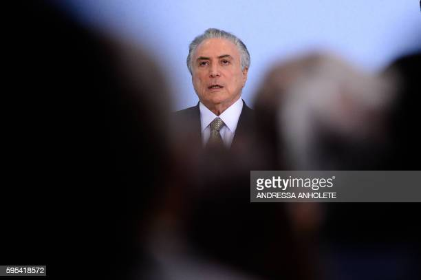 Brazilian acting President Michel Temer delivers a speech during the reception ceremony of the Paralympic Torch at Planalto Palace in Brasilia on...