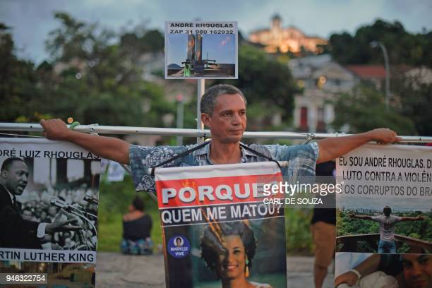 Brazilian activist against corruption Andre Rhouglas carries a cross with hanging banners during a demonstration marking one month of activist...