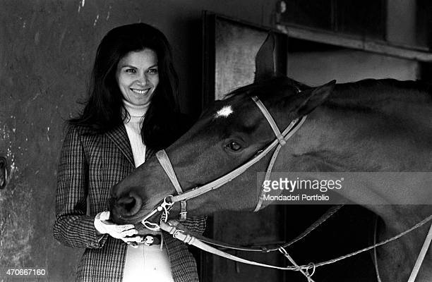 Brazilian actress Florinda Bolkan Florinda Soares BulcÆo's stage name pets a horse smiling inside the riding stables of Tor di Quinto after having...