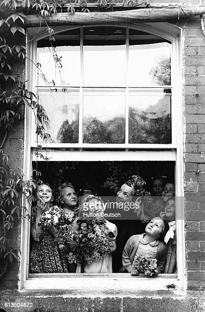 Brazilian actress singer and dancer Carmen Miranda with a group children wait for the rain to stop during May Day celebrations in Weston Turville...