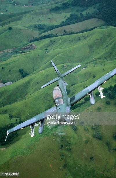 Brazilian Air Force Embraer EMB314 Super Tucano banking over fields and trees