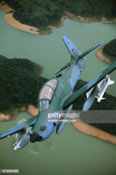 Brazilian Air Force Embraer EMB314 Super Tucano banking over river and trees