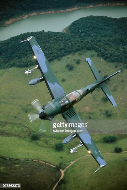 Brazilian Air Force Embraer EMB314 Super Tucano banking over river fields and trees