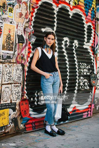 Brazilian Alexia Bellini wears a silk scarf around her neck a slip top over a white tshirt tucked into jeans with frayed hems and white socks with...