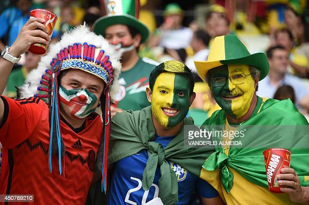 Brazilian and Mexican fans pose prior to a Group A football match between Brazil and Mexico in the Castelao Stadium in Fortaleza during the 2014 FIFA...