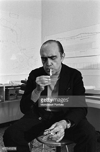 'Brazilian architect Oscar Niemeyer lighting a cigarette in his studio The Italian publisher Giorgio Mondadori has recently commissioned the...