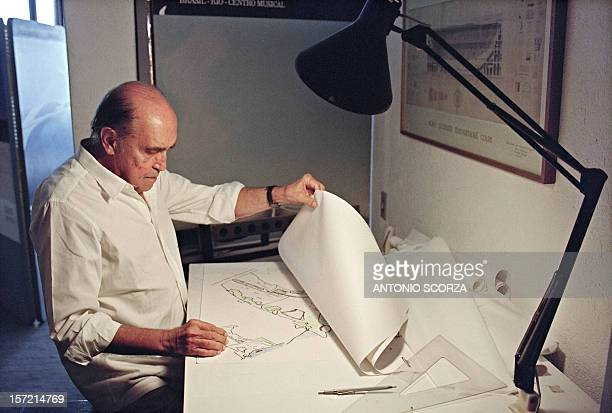 Brazilian architect Oscar Niemeyer looks at drawings for a project of two cities in Senegal Africa in his office in Rio de Janeiro 23 January 1992