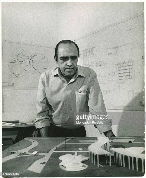 'Brazilian architect Oscar Niemeyer observing the scale model of Palazzo Mondadori in his office Behind him the drawings of some projects hanging...