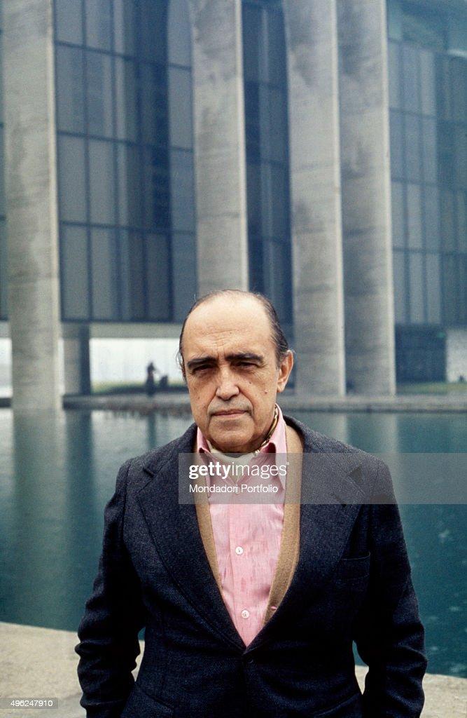 Brazilian architect Oscar Niemeyer posing outside the Mondadori Palace he designed. Segrate, 1976