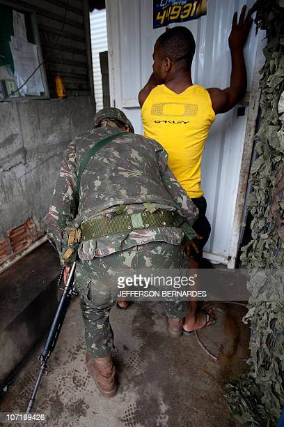 A Brazilian Army soldier frisks a resident at the entance to Moroo do Alemao shantytown on November 27 2010 in Rio de Janeiro Brazil Rio's slums saw...