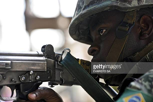 A Brazilian Army soldier holds a rifle as he stands guard at the entrance of the Morro do Alemao shantytown on November 27 2010 in Rio de Janeiro...